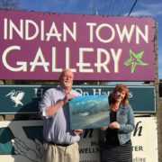 April Trueblood, owner of Indian Town Gallery, and Bob Muller, Board Member, Outer Banks Community Foundation, hold a painting by Wayne Fulcher.